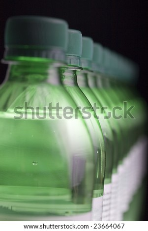 Row of green bottles of sparkling water, with shallow depth of field. The second bottle is in focus.