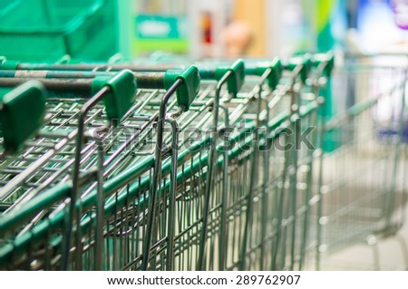 Row of green shopping carts in front of entrance to supermarket