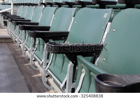 Row of green stadium seats folded up.