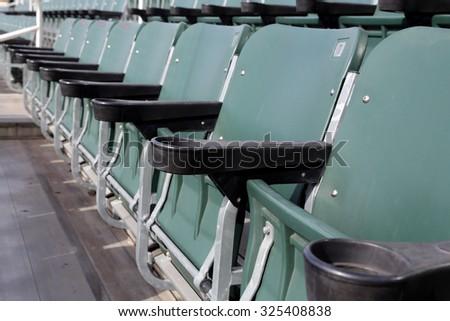 Row of green stadium seats folded up. - stock photo