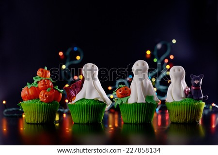 Row of Halloween cupcakes decorated with sugar ghosts and pumpkins side view. - stock photo