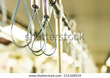 row of handles for standing passenger in electric train in thailand. Selective focus - stock photo