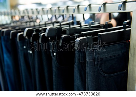 Row of hanged blue and black jeans in a shop