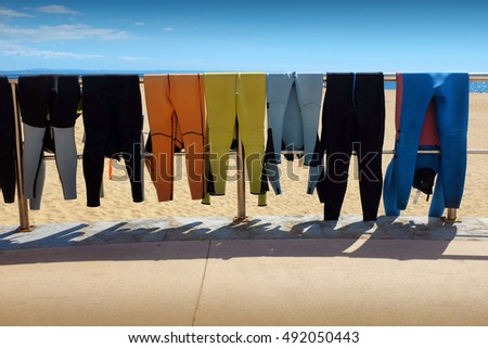 Row of hanging surfing wet suits drying under the sun at the beach