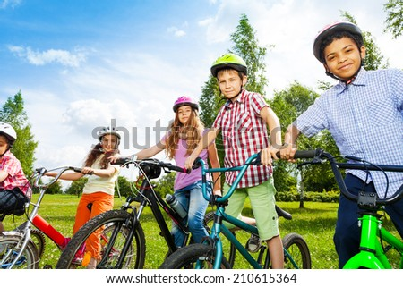 Row of happy children in bike colorful helmets - stock photo