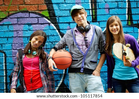Row of happy teens by painted wall looking at camera - stock photo