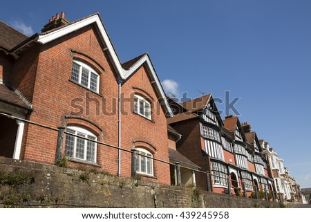 Row of houses in a typical English town. Mixed styles of architecture on this suburban street.