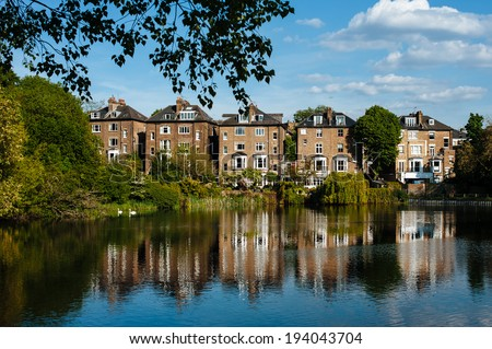 Row of houses near to Hampstead Heath in London with a blue sky and reflected in the water.