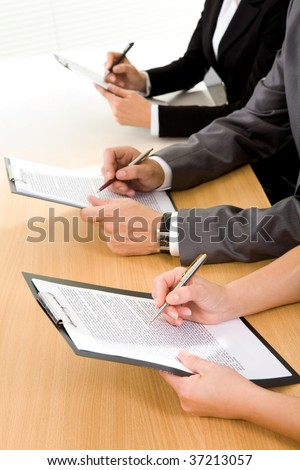 Row of human hands over papers reading business documents