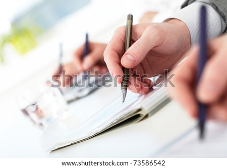 Row of human hands with pens making notes during conference