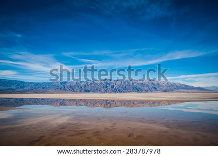 Row of imposing mountains stands above and is reflected in the rare pool of water at the bottom of Death Valley. - stock photo