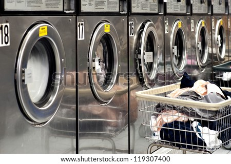 Row of industrial washing machines in a public laundromat, with laundry in a basket - stock photo