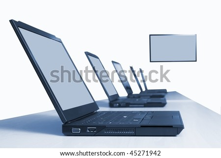 Row of laptops in training room with video conferencinig widescreen - stock photo
