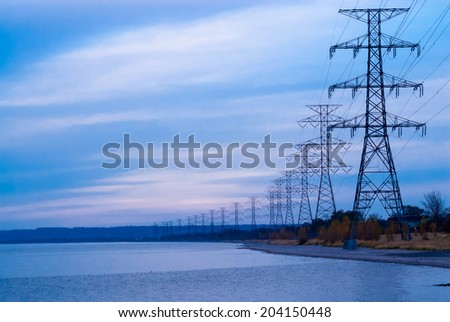 Row of large electrical towers receding into distance by shore. - stock photo