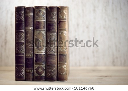 Row of leather vintage books on shelf - stock photo
