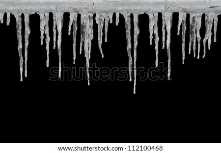 Row of long icicles on black background - stock photo