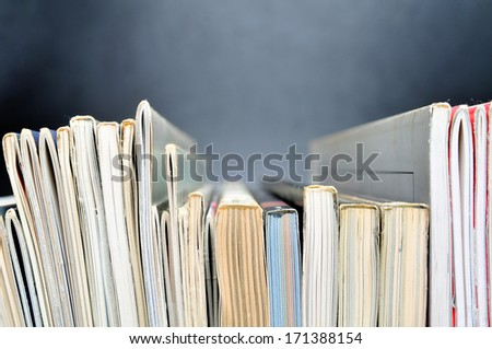 Row of magazines in front of black background - stock photo