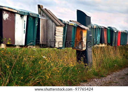 Row of mailboxes in rural summer village - stock photo