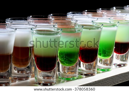 Row of many colorful vivid green red orange colored alcohol tasty cocktail shooters drinks in drinking glasses standing on white bar on black background closeup studio, horizontal picture - stock photo
