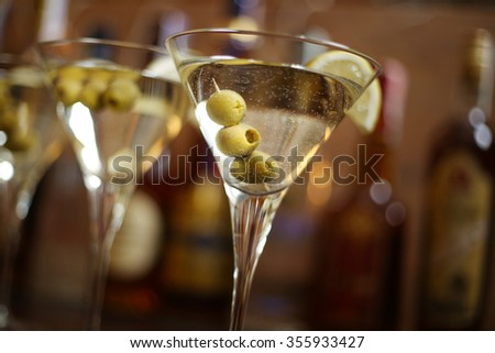 Row of martini glasses, a slice of lemon and green olives on the bar in the background of bottles with alcohol. New Year celebration or other event.