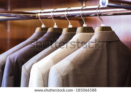 Row of men's suit jackets hanging in closet