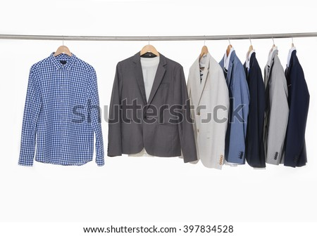 Row of men's suits hanging on the white background - stock photo
