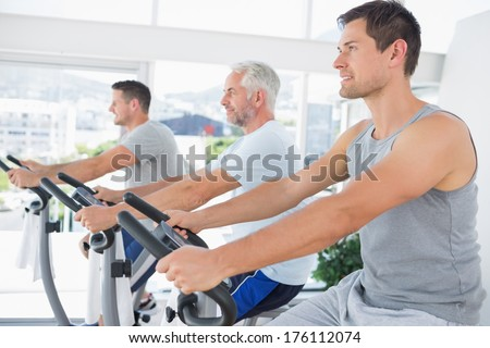 Row of men working out on exercise machines at fitness studio