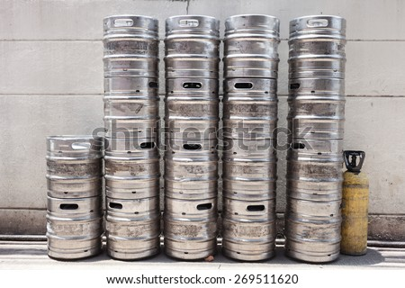 row of  metal beer kegs against a light pink wall . - stock photo