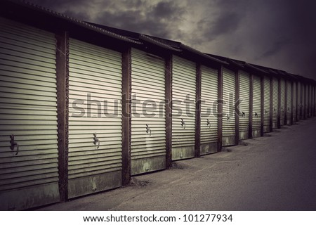 Row of metal garage doors in run down residential area - stock photo