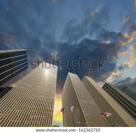 Row of modern skyscrapers in New York. Upward view of Manhattan buildings at sunset. - stock photo