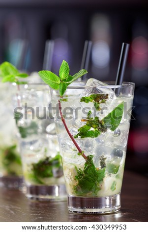 Row of Mojito cocktails on a bar counter in a club. Vertical shot