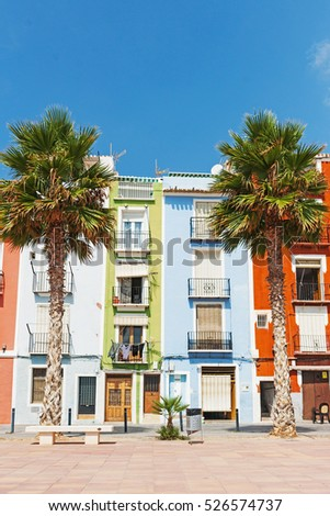 Row of multi-colored terrace homes between palms at La Vila Joiosa, Costa Blanca Spain.