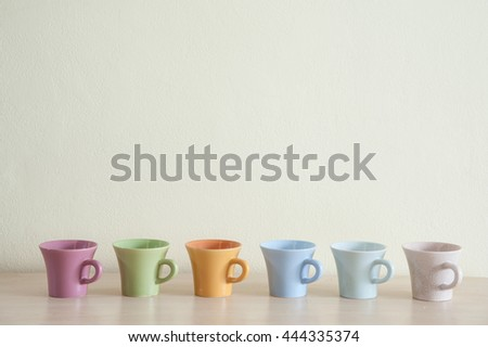 Row of multicolor coffee cups on clear background. Top space frame.