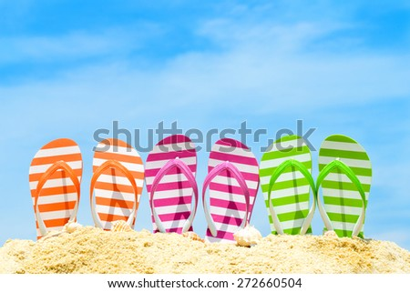 Row of multicolor flip flops on beach against blue sky