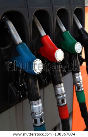 Row of multicolored fuel pumps.focus foreground