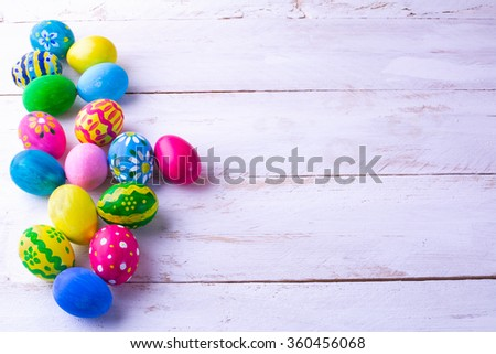 Row of multicolored hand-painted Easter eggs on white wood plank. Easter background. Easter symbol. Top view with copy space - stock photo