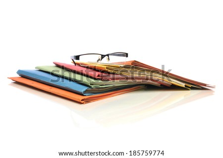 Row of multicolored office folders with glasses on white background - stock photo