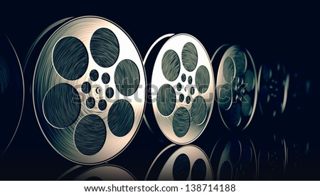 Row of new reflective film spools with tape on dark background. - stock photo
