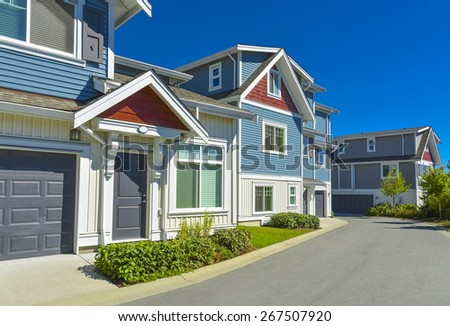 Row of new residential townhouses on a street on sunny day. Family townhouses with concrete driveway and asphalt road in front. British Columbia, Canada. - stock photo