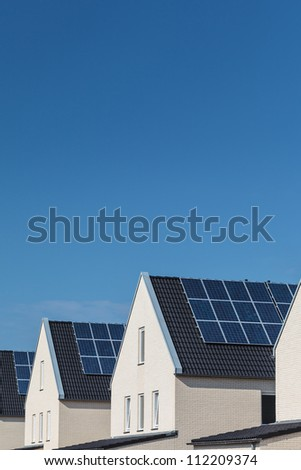 Row of new white houses with solar panels on the roofs in a row