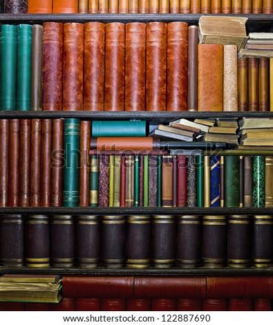Row of old books arranged in bookshelves - stock photo