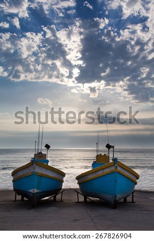 Row of old fishing boats in a small harbour next to the ocean in the morning - stock photo