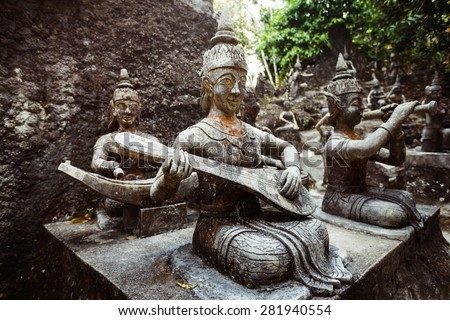 Row of old statues in secret buddhist garden. Concept of mysterious place for relaxation and meditation. - stock photo