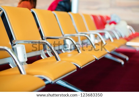 Row of orange seats with electric socket in airport - stock photo