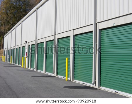 Row of outdoor green door self-storage units - stock photo