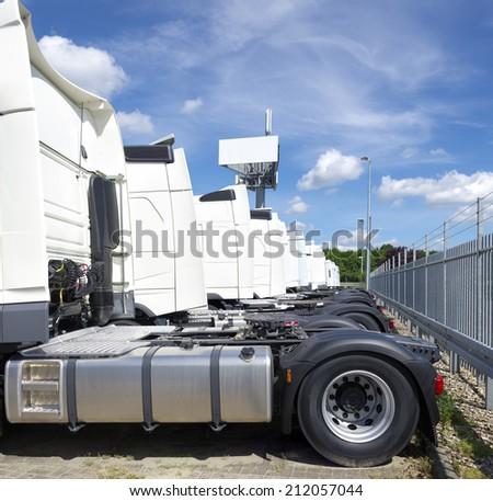 row of parked white trucks  - stock photo