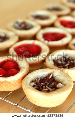 Row of Pecan and Cherry Pie Tarts Cooling on a Rack - stock photo