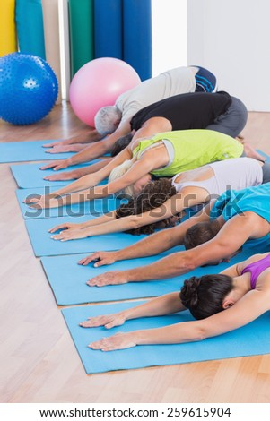 Row of people practicing child pose on exercise mats in gym - stock photo