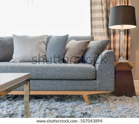 row of pillows on grey sofa with black lamp in living room design