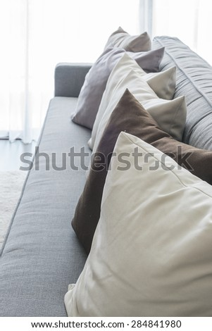 row of pillows on modern grey sofa in living room